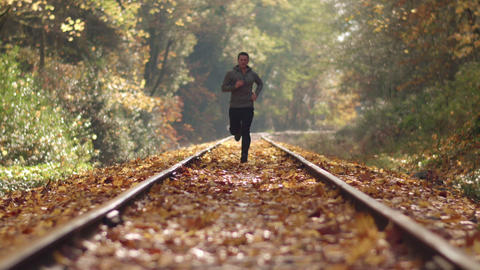 Man Jogging Up Train Tracks In Autumn Season With Leaves Falling And Deep Focus stock footage