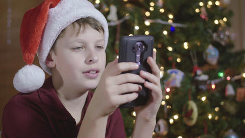 Young Boy Wearing Santa Hat Sending And Receiving Text Message On Cell Phone By stock footage