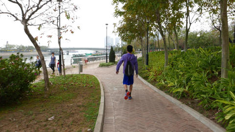 Boy with basketball walking on riverside promenade, training, throwing ball up Footage