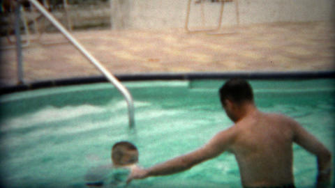 1955: Dad Teaching Son To Swim In Pool As Child Jumps In With Enthusiasm stock footage