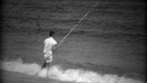 1936: Kid beach shore fishing on gulf bay waters with long pole Footage