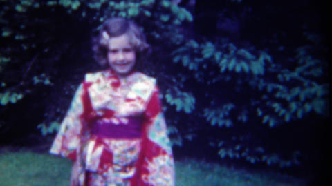 1949: Little caucasian girl in eastern asian kimono style winged dress Footage