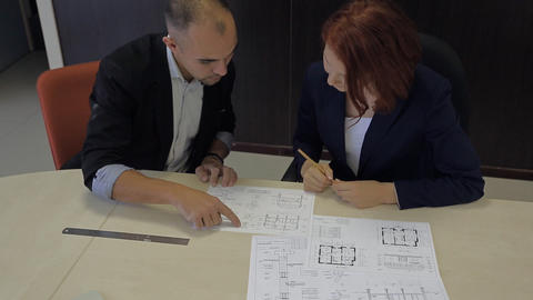 Male And Female Professionals Working Together On A Blueprint House Schemes stock footage