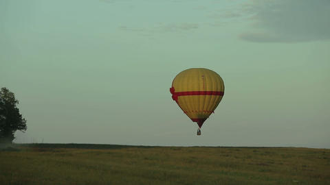 Hot Air Balloon Flying Over Field In Countryside stock footage