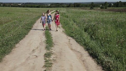 Mother With Daughters Walk On Rural Road To Field stock footage