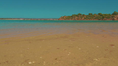 Low Angle Beach Shore Shot Turquoise Water In The Algarve, Portugal stock footage