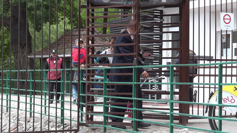 People Passing Through A Rotating Gate At The Exit Of An Outdoor Museum 58 stock footage