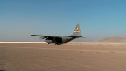 C-130 Hercules Taking Off From Dusty Air Strip stock footage