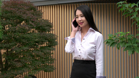 Beautiful Asian Woman Talking On Mobile Phone Near Office Building Footage