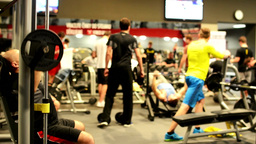 Man Strengthens On The Machine In The Fitness Center, Other Athletes In Backgrou stock footage
