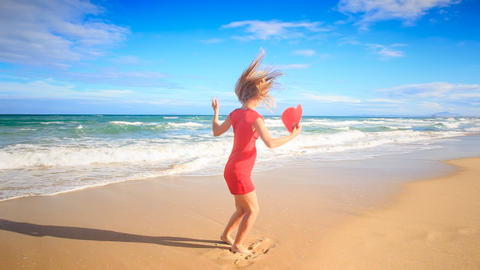 Blond Slim Girl Jumps Plays With Red Heart On Surf In Red stock footage