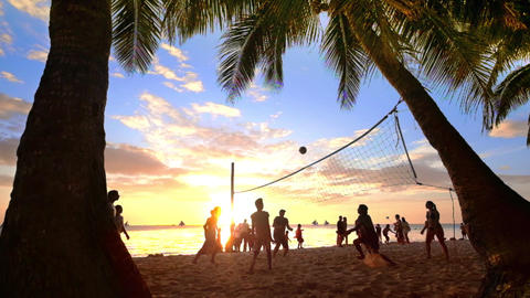 Slow motion. Sunset silhouette of people playing volleyball at tropical beach un Footage