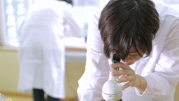 Female Lab Tech Looking Into Microscope stock footage