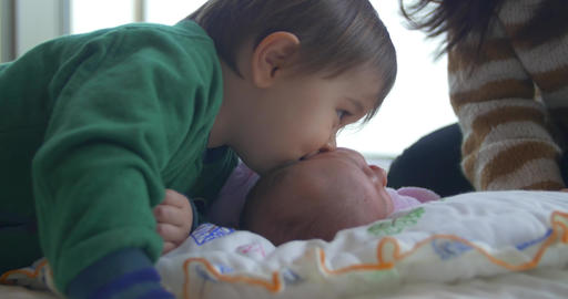 Child Of Asian Decent Kissing His Baby Sister stock footage