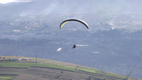 Tandem Paragliding Flying Over Rural Area In Andes stock footage