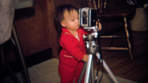 1971: Toddler photographer learning the craft looks at 8mm movie camera Footage