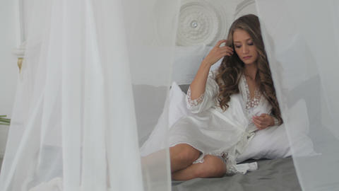 Beautiful Young Woman In White Bathrobe In Bedroom At Home stock footage