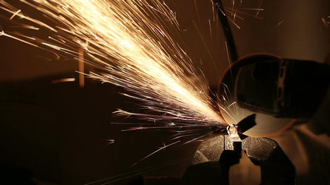 Sparks Fly While The Man Cutting A Metal Rod With A Grinding Machine stock footage