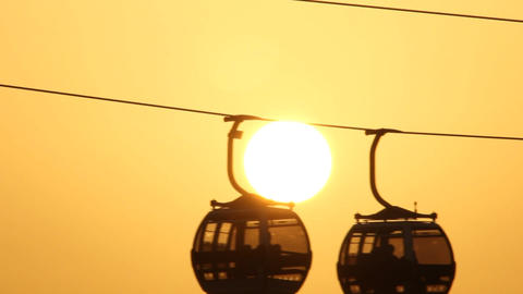 Two gondola lift slide against brisk sun disk, telephoto view Footage