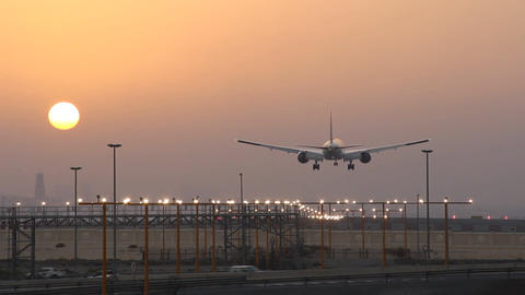Airliner land against sunset, approach lighting system blink in runway direction Footage