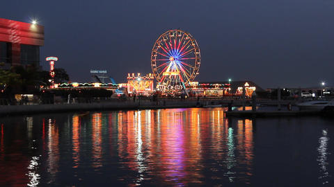 Colorful lights and Ferris wheel reflection in water surface, time lapse Footage