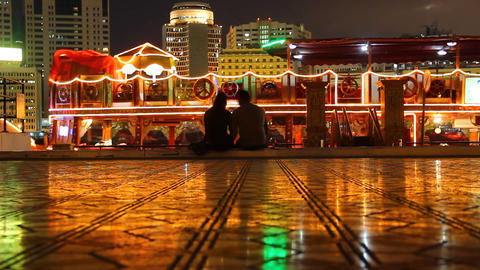 Couple Silhouette Against Bright Dinner Cruise Dhow, Creek Promenade At Night stock footage