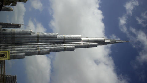 Burj Khalifa supertall skyscraper against blue sky and fast clouds, time lapse Footage