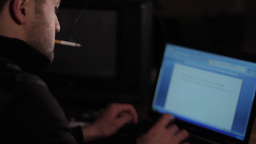 Male Writer At Night Smoking A Cigarette, And Prints The Story On The Laptop Key stock footage