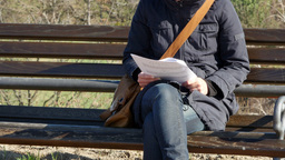 ZOOM OUT on a young woman reading on the park bench Footage