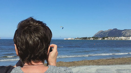 Woman Shooting Kite Surfers On Port De Pollenca's Beach stock footage