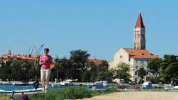 Woman Taking Photos And Walking Towards The Camera Trogir Old Town Background stock footage