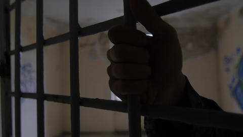 Hand on cell bars in cracked jail Footage