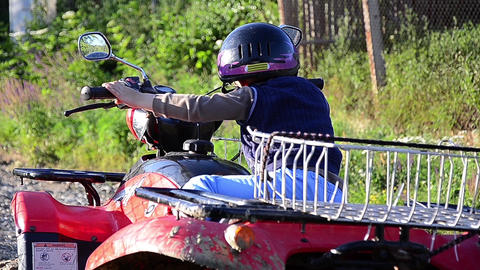 Child With Black Helmet In The Head Sitting On An ATV And Mimicking As He Leads  stock footage