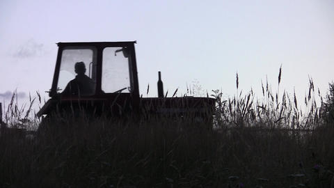 Tractor Mowing High Grass Grown On Land Behind The House, Seen Through Dry Grass stock footage