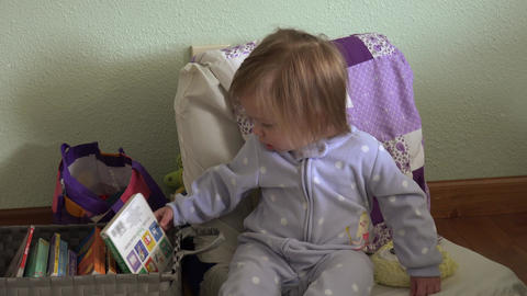 Baby shaking head no being silly on small chair looking at books Footage