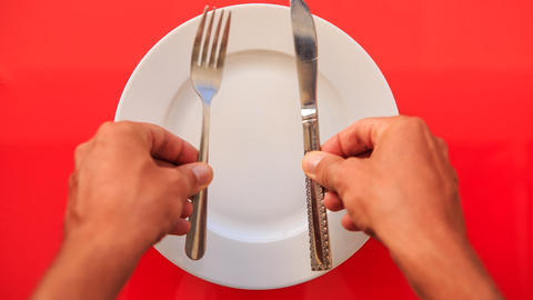 Hands Put Fork Knife Vertically On Plate On Red Table stock footage