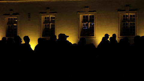 Black Silhouettes Of People Who Watch A Show Projected On The Yellow Wall Of A B stock footage