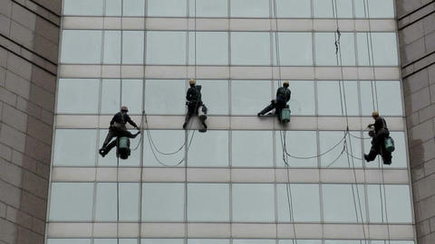 Window Cleaner Cleaning A Glass Façade Of A Department Store stock footage