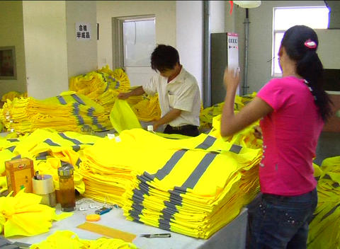 Factory Workers Folding Jackets stock footage