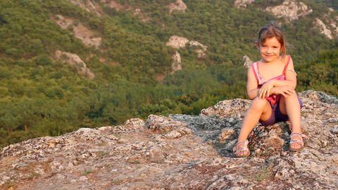 Little Girl Sitting On A Mountain Top stock footage
