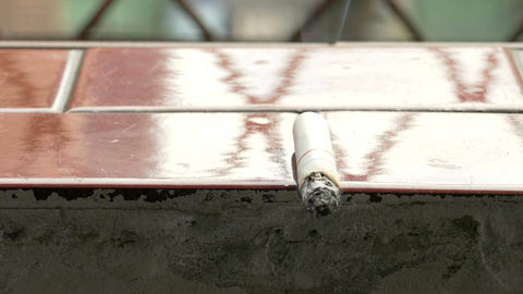 Lit Cigarette On Ledge 2 stock footage