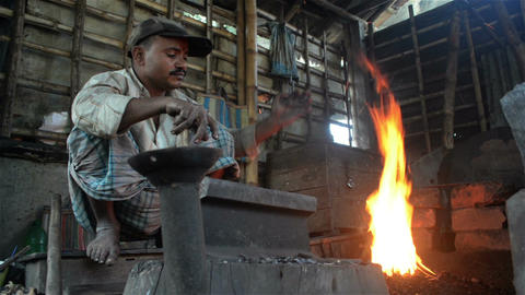 A Candid Wide Shot Of An Indian Blacksmith Doing His Daily Job stock footage