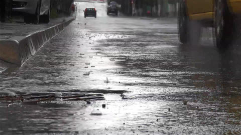 Rain with big drops that break the asphalt street while cars go speed 6 Footage
