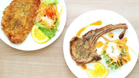 Battered Fish Steak And Grilled Pork Chop Steak With Bone. Colourful Salad And V stock footage