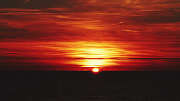 Beautiful Red Sunset Over The Sea With Red Clouds, The Sun Disappears Behind The stock footage