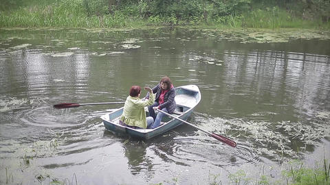 Two Women Floating In A Boat On The River stock footage