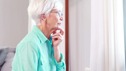 Thoughtful Senior Woman Looking Through Window stock footage