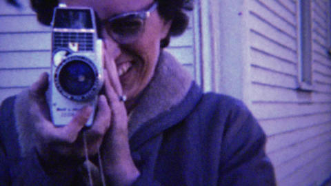 1961: 60's style eyeglasses women filming 8mm movie camera Footage