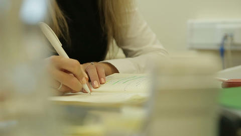 Closeup of business woman writes a pen in daily, wooden table Footage