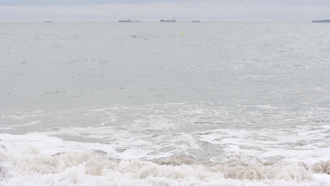 Focus On Waves With Tankers In Distance stock footage